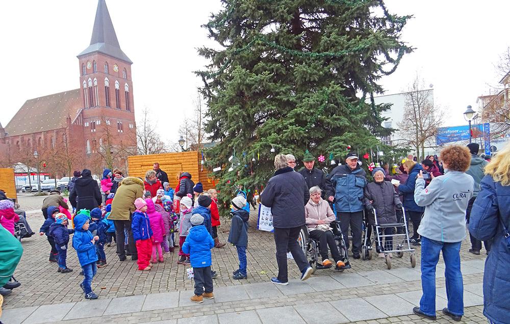 Jung und Alt schmücken Weihnachtstanne auf dem Pasewalker Markt